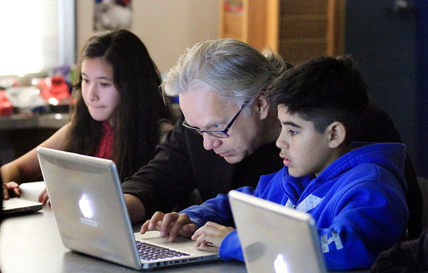 Sixth grader shows actor Tim Robbins his project on Photoshop Elements as classmate works next to them during their visual arts class at Burbank Elementary School in Hayward, Calif., on Friday, Feb. 20, 2015.  (Laura A. Oda/Bay Area News Group)