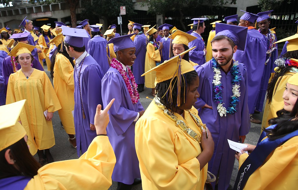 . Lauren Brouhard-Chuck, left, points to Liam Barney, right, as they line up to enter Oakland Technical High School graduation ceremonies at the Paramount Theatre in Oakland, Calif., on Tuesday, June 11,  2013. The school graduated 351 students in the class of 2013. (Jane Tyska/Bay Area News Group)