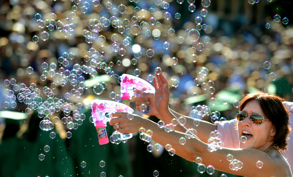 . Monika Fahlbusch, of Danville, lets loose a barrage of bubbles with a bubble gun as her son and the other San Ramon Valley High School graduates walk onto the football field for their Commencement Ceremony in Danville, Calif., on Friday, June 14, 2013. (Doug Duran/Bay Area News Group)