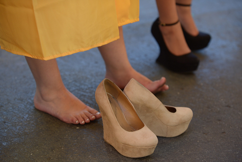 . Ygnacio Valley High School student Geraldine Flores, 18, takes a break from her high heels before commencement ceremonies at Sleep Train Pavilion in Concord, Calif., on Thursday, June 13, 2013. (Jose Carlos Fajardo/Bay Area News Group)