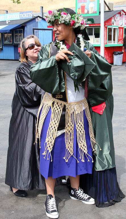 . Instructor Lorie Johnson, left,  helps student Ana Fifita with the sash of her traditional Tongan school uniform that she wore to graduation ceremonies for Mt. Diablo High School held at the Sleep Train Pavilion in Concord, Calif., on Sunday, June 9, 2013. It is the 100th anniversary of the school,  which graduated three students in 1913 and 300 on Sunday. (Jim Stevens/Bay Area News Group)