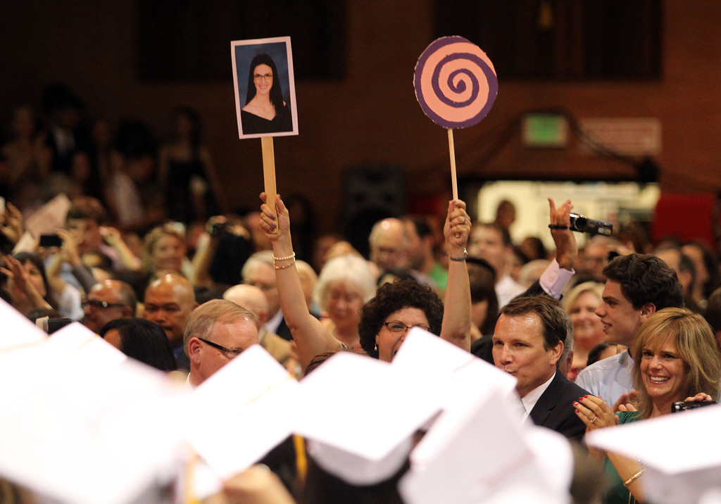. A member of the audience cheers with a photo of a Carondelet High School graduate of the Class of 2013 at the conclusion of the commnecement ceremony at Carondelet High School in Concord, Calif., on Sunday, May 19, 2013. (Ray Chavez/Bay Area News Group)