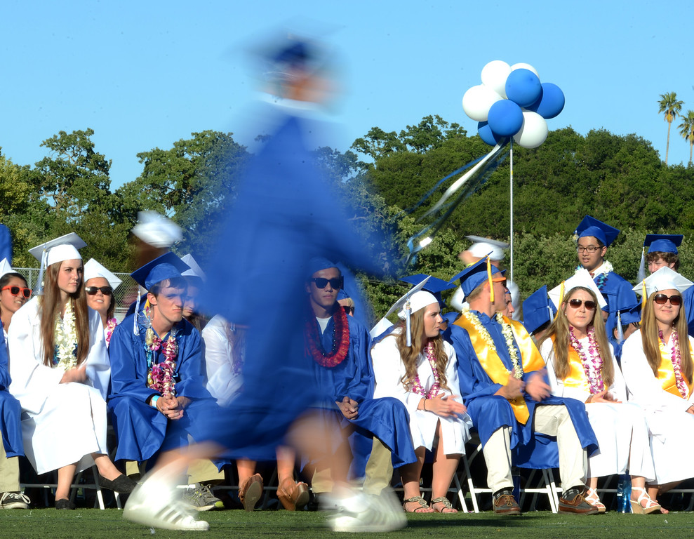 . An Acalanes High School graduate walks past other classmates as he gets his diploma during the commencement ceremony in Lafayette, Calif., on Friday, June 7, 2013. The graduation featured speeches from graduates Edward Huddart and Carolyn Moore. (Doug Duran/Bay Area News Group)