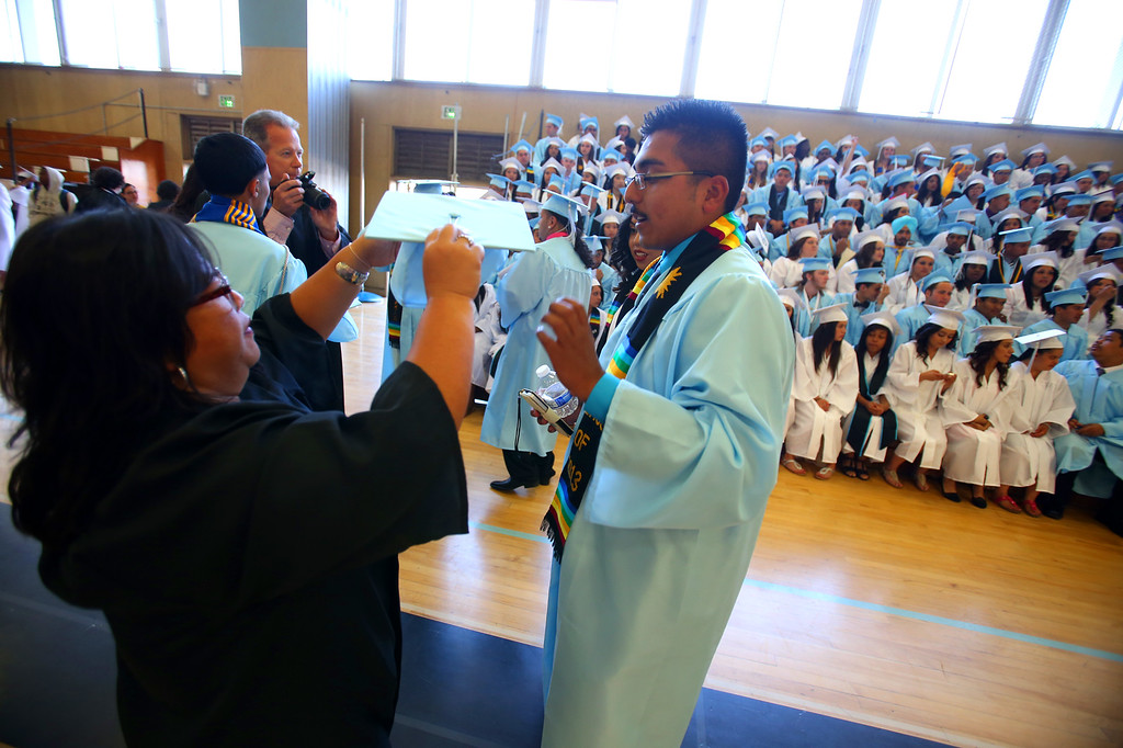 . Tennyson High School teacher Donna deLeon, left, helps graduate Gerardo Duran, right, with his cap before commencement ceremonies on Thursday, June 13, 2013 in Hayward, Calif.  (Aric Crabb/Bay Area News Group)