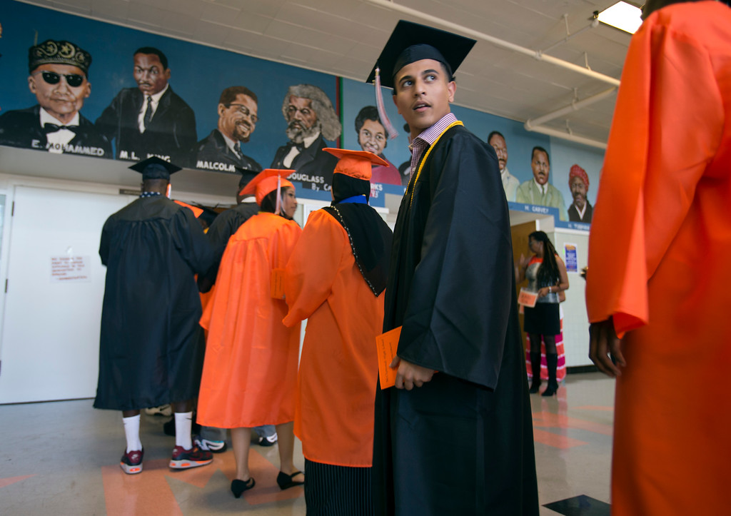 . Easom Saeed, right, looks around as he waits to process with his classmates at the graduation ceremonies for the Class of 2013 at McClymonds High School, Thursday, June 13, 2013 in Oakland, Calif. (D. Ross Cameron/Bay Area News Group)
