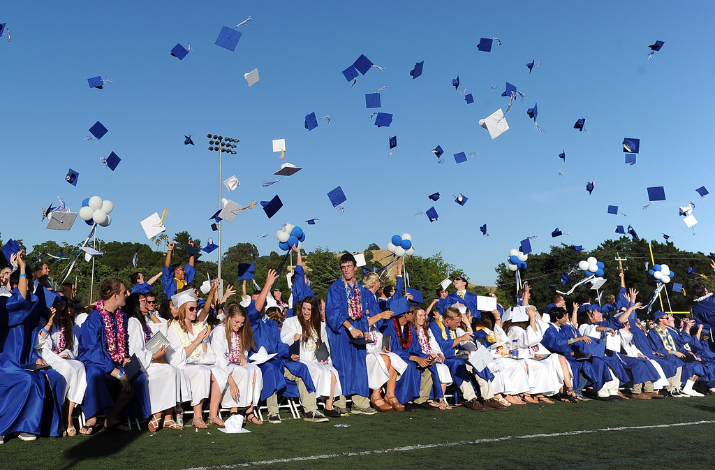 . Acalanes High School graduates throw their mortarboards into the air at the conclusion of their commencement ceremony in Lafayette, Calif., on Friday, June 7, 2013. The graduation featured speeches from graduates Edward Huddart and Carolyn Moore. (Doug Duran/Bay Area News Group)