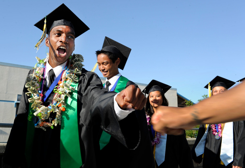 . Senior Montel Anthony Nord of Antioch reaches out to his cousin Tre Bell of San Francisco during the procession of the Dozier-Libbey Medical High School 2013 Commencement Ceremony held at Deer Valley High School in Antioch, Calif., on Wednesday, June 5, 2013. (Susan Tripp Pollard/Bay Area News Group)