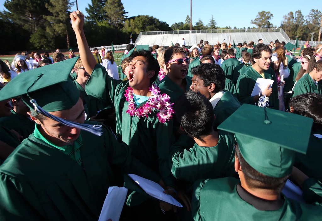 . Korey Sop, left center, celebrates with classmates during Miramonte High School\'s 54th commencement ceremony in Orinda, Calif., on Friday, June 7, 2013. Graduates, friends and family endured very hot temperatures during the ceremony. (Jane Tyska/Bay Area News Group)