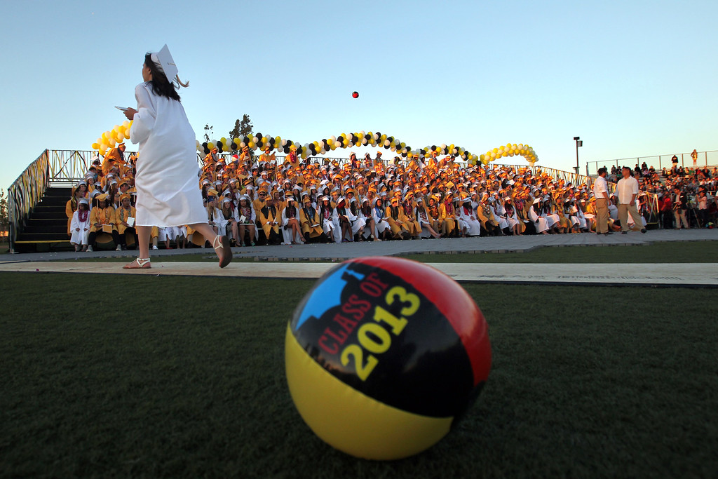 . A senior of the Class of 2013 walks back to the stands after receivng her diploma during the Alameda High School graduation ceremony at the College of Alameda soccer field in Alameda, Calif., on Friday, June 7, 2013.  (Ray Chavez / Bay Area News Group)