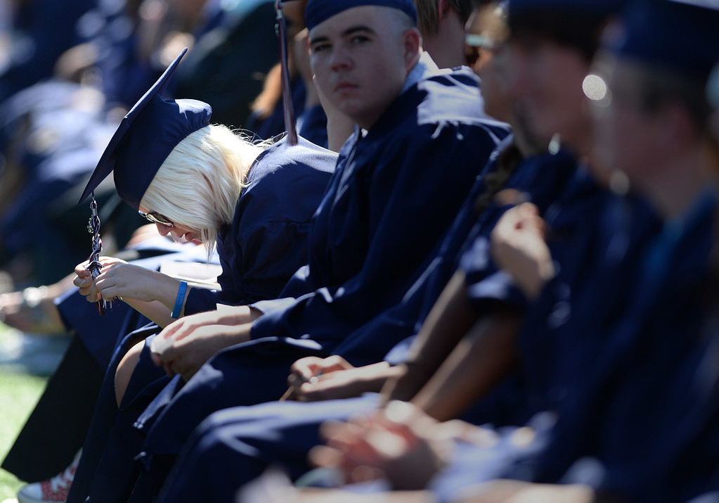 . A graduate braids her hassle as she waits for the festivities to begin at the Freedom High School graduation ceremony held at Falcon Stadium on the campus of Freedom High School in Oakley, Calif., on Saturday, June 8, 2013. (Dan Honda/Bay Area News Group)
