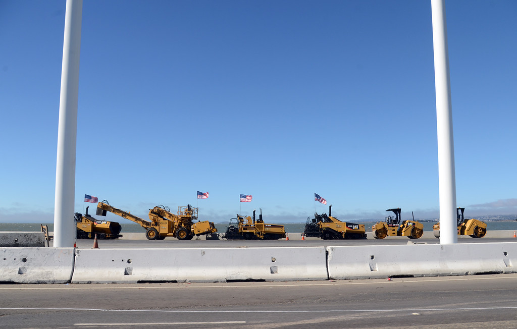 Description of . Flag-bearing construction equipment stages at the foot of the new Bay Bridge in Oakland, Calif., on Wednesday afternoon, Aug. 28, 2013, ready to race to work after the 8 p.m. closure to reconfigure the roadway from the toll plaza to the new Bay Bridge skyway.  (Karl Mondon/Bay Area News Group)