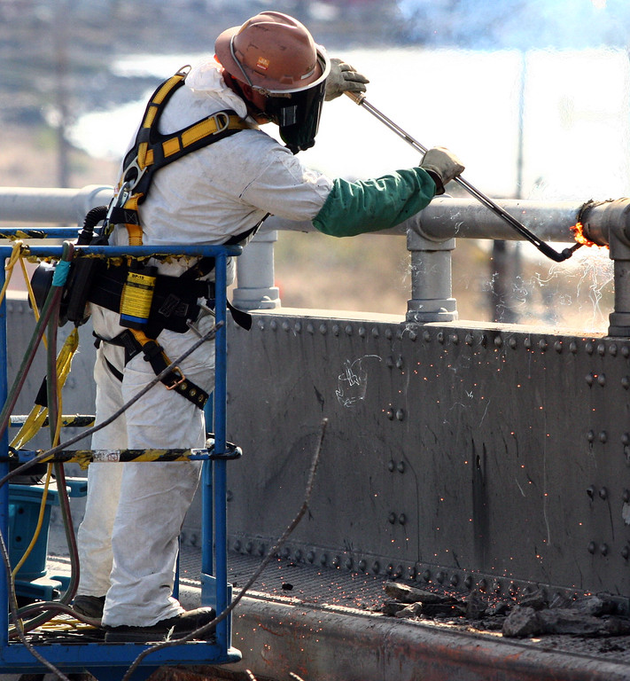 Description of . A worker uses a cutting torch as demolition of the old Bay Bridge continues in Oakland, Calif., on Saturday, Aug. 31, 2013. According to Caltrans, progress continues to remain on schedule on the third day of the bridge closure. (Anda Chu/Bay Area News Group)