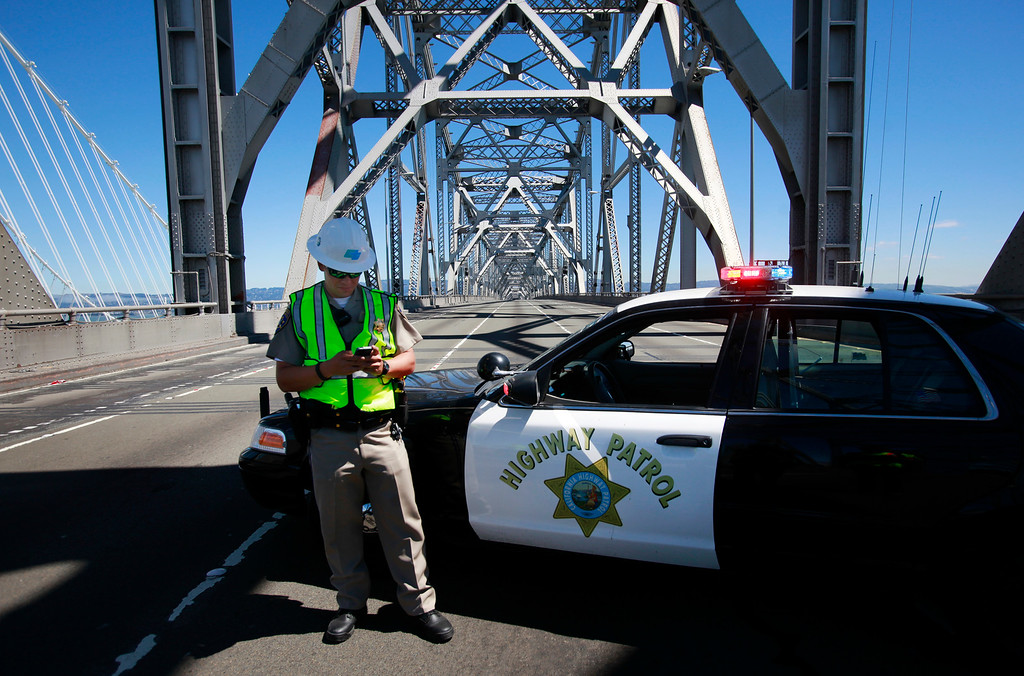 Description of . California Highway Patrol officer Daniel Hill stands guard on the closed old Bay Bridge on Thursday, Aug. 29, 2013 one day after the 76-year-old span was retired in San Francisco, Calif.  (Karl Mondon/Bay Area News Group)