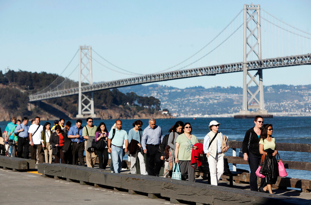 Description of . With the closed Bay Bridge serving as a backdrop, afternoon commuters wait for the Harbor Bay Ferry on Thursday, Aug. 29, 2013, in San Francisco, Calif. (Karl Mondon/Bay Area News Group)