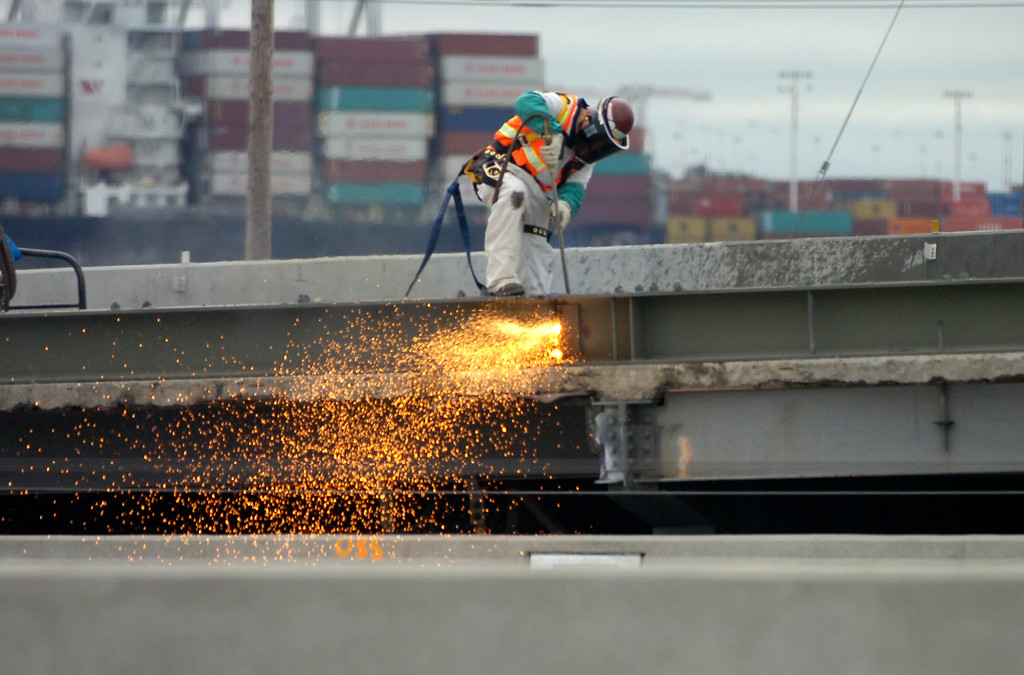 Description of . A worker uses a cutting torch as the demolition work gets underway on the old span of the Bay Bridge in Oakland, Calif. on Thursday, Aug. 29, 2013. (Kristopher Skinner/Bay Area News Group)