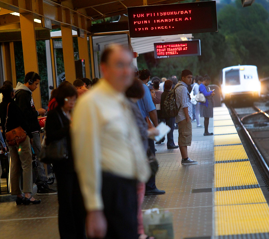 Description of . Passengers wait for a train on a platform at the Hayward BART station on Thursday, Aug. 29, 2013, in Hayward, Calif.  (Aric Crabb/Bay Area News Group)
