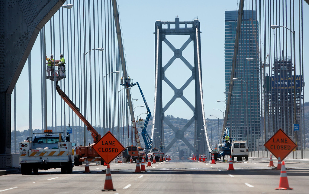 Description of . With the five-day bridge closure in place, maintenance crews work Friday morning, Aug. 30, 2013 painting suspender ropes and fixing the Bay Light's installation on the original Bay Bridge's western span in San Francisco, Calif. (Karl Mondon/Bay Area News Group)