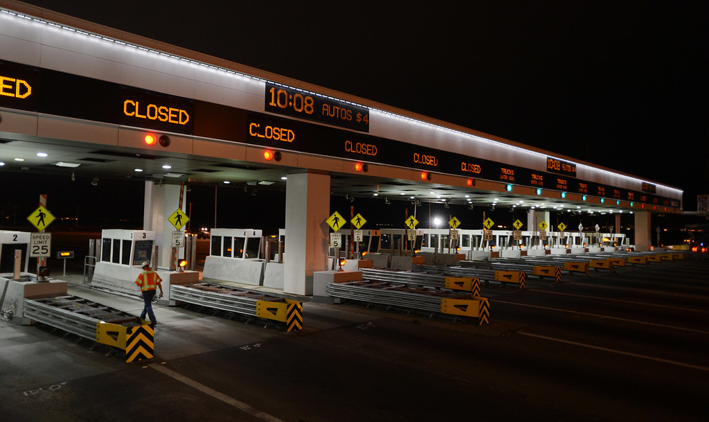 Description of . A Caltrans worker walks through the closed toll plaza at the Bay Bridge in Oakland, Calif., on Wednesday, Aug. 28, 2013. (Susan Tripp Pollard/Bay Area News Group)