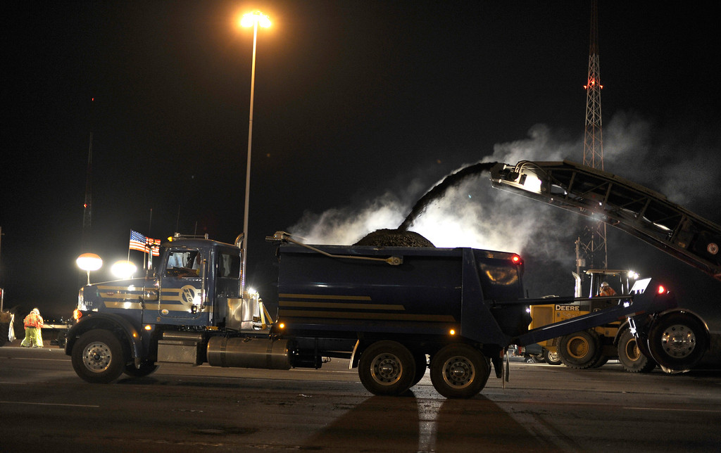 Description of . Steam rises from hot asphalt as work takes place in front of the toll plaza on the Bay Bridge in Oakland, Calif., on Wednesday, Aug. 28, 2013.  (Susan Tripp Pollard/Bay Area News Group)