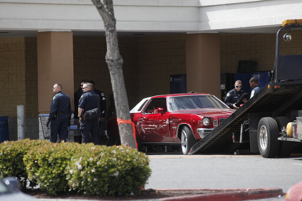 Description of . Police tow away a red Cutlass Salon that was driven into a Walmart Store on Story Road in San Jose, Calif., on Sunday, March 31, 2013. (Karl Mondon/Staff)