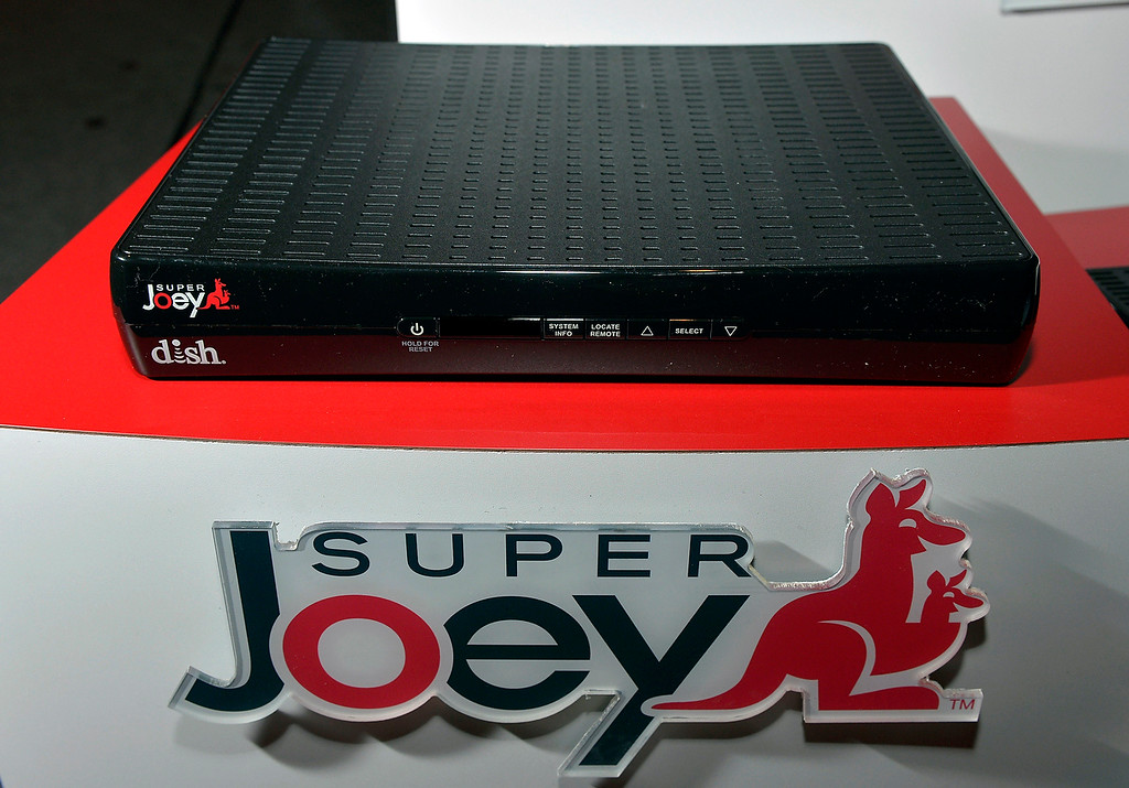 Description of . Dish shows off the new Super Joey during the Dish news conference at the International Consumer Electronics Show Monday, Jan. 6, 2014, in Las Vegas. The Super Joey allows the user to record eight different programs at the same time. (AP Photo/Jack Dempsey)