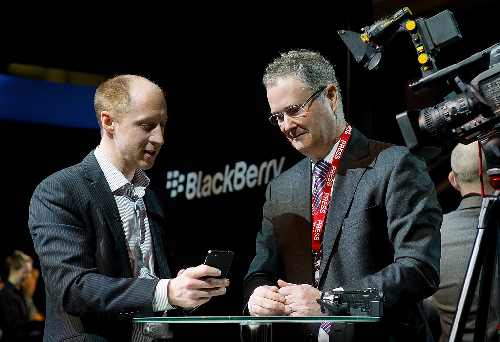 Description of . A member of the RIM team (L) demonstrates one of the new touchscreen Z10 Blackberry devices to a television crew in central London at one of eight simultaneous worldwide events for the launch of the BB10 operating system on January 30, 2013. (LEON NEAL/AFP/Getty Images)