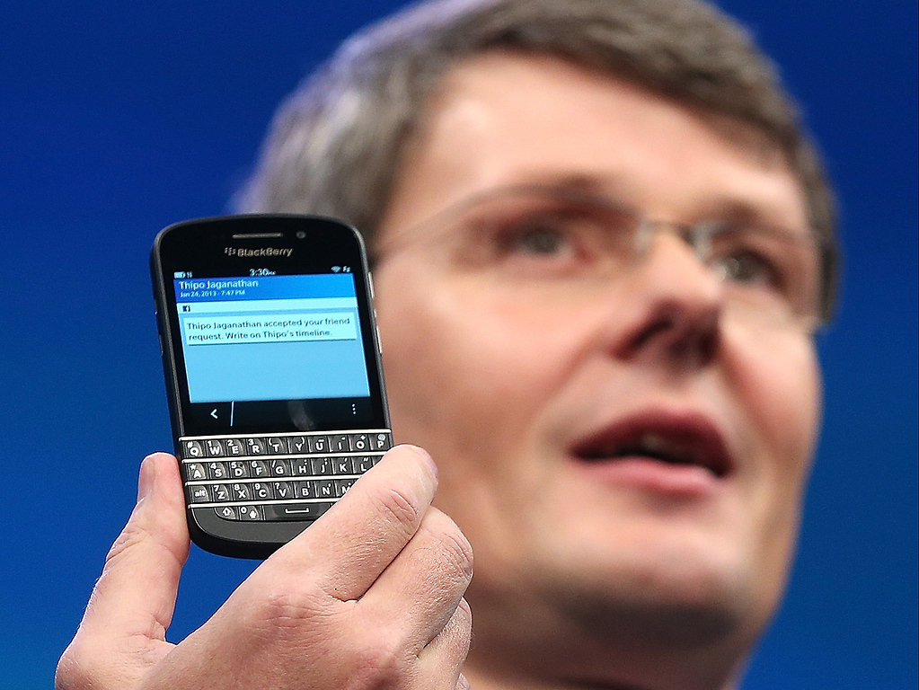 Description of . BlackBerry Chief Executive Officer Thorsten Heins displays one of the new Blackberry 10 smartphones with a physical keyboard at the BlackBerry 10 launch event by Research in Motion at Pier 36 in Manhattan on January 30, 2013 in New York City. The new smartphone and mobile operating system is being launched simultaneously in six cities.  (Photo by Mario Tama/Getty Images)