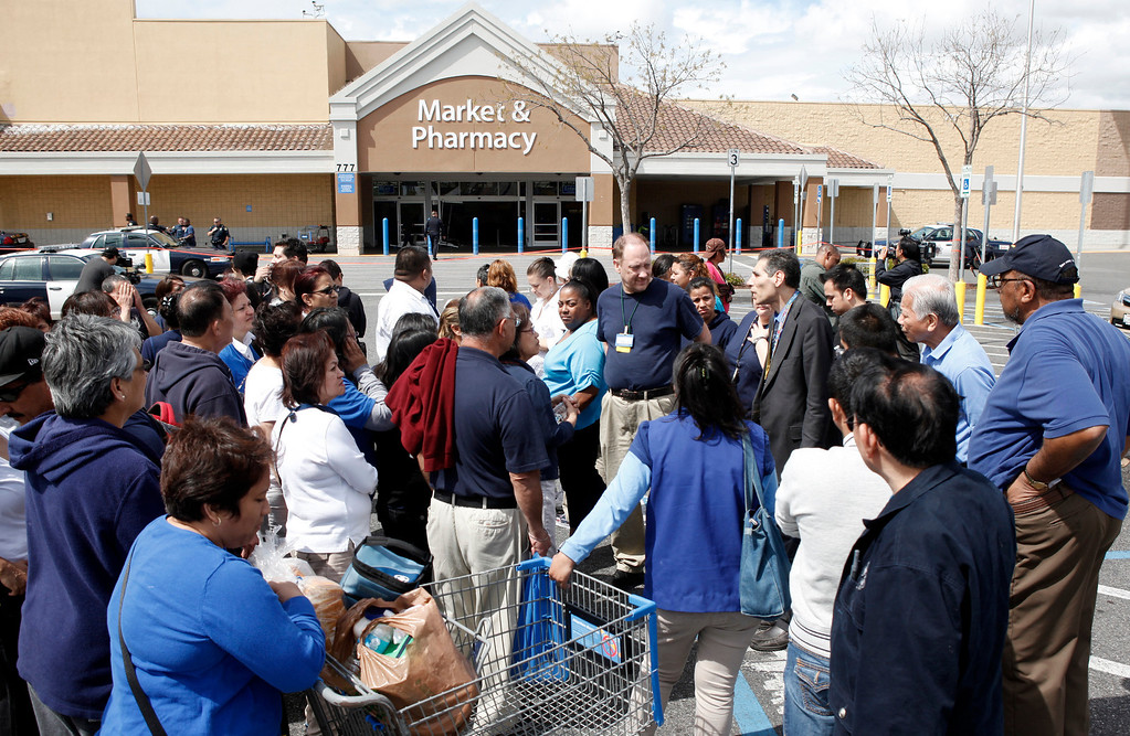 Description of . Walmart employees huddle around for word about one of their colleagues injured in an incident where a red Cutlass Salon was driven into the business on Story Road in San Jose, Calif., Sunday afternoon March 31, 2013. (Karl Mondon/Staff)