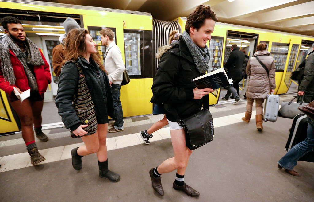 Description of . People without their pants exit a subway train during the