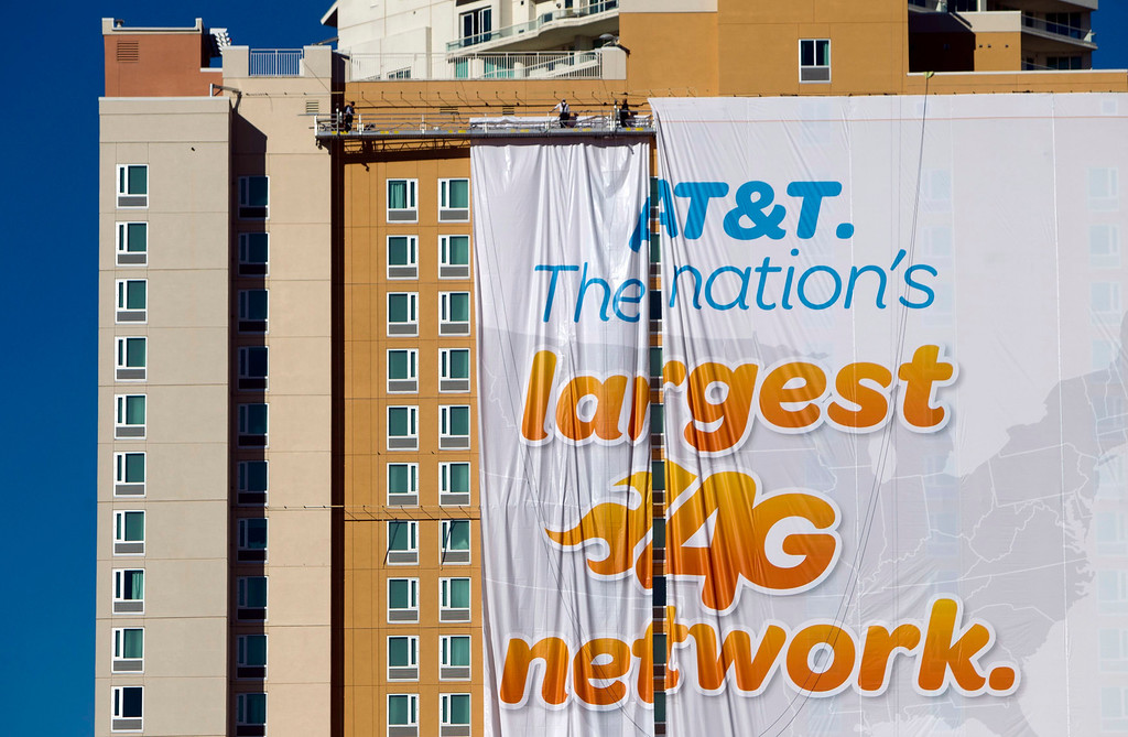 Description of . Workers put up a banner advertisement for AT&T on the side of a hotel as they prepare for International CES show in Las Vegas, Nev., on Jan. 4, 2013. (REUTERS/Steve Marcus)
