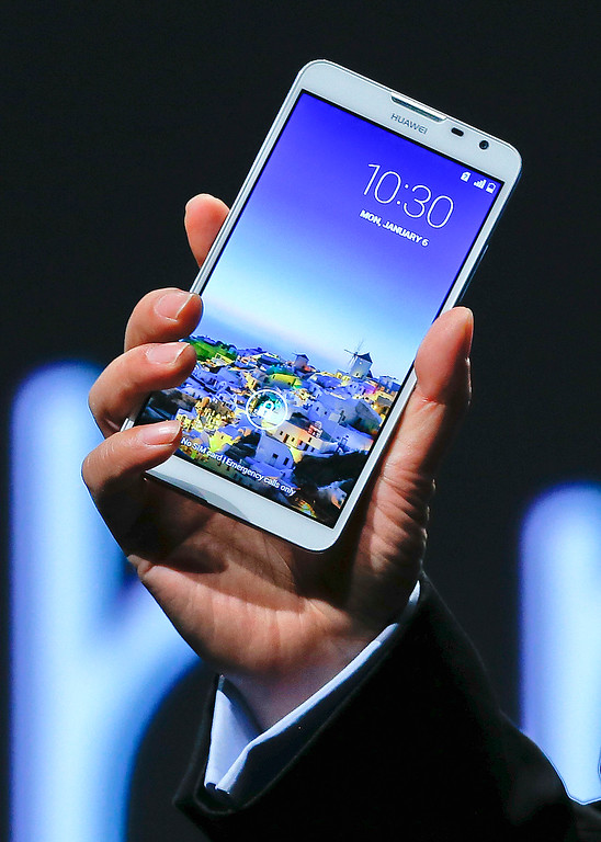 Description of . Huawei Consumer Business Group CEO Richard Yu holds up the Ascend Mate 2 4G smartphone at a news conference during the International Consumer Electronics Show, Monday, Jan. 6, 2014, in Las Vegas. (AP Photo/Julie Jacobson)