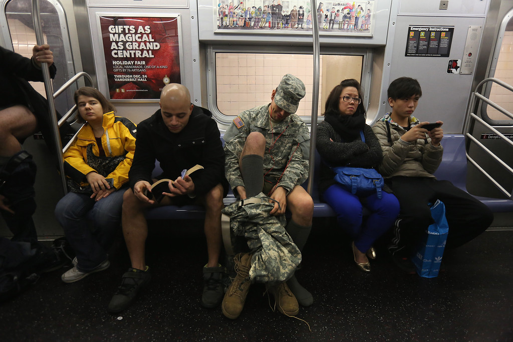 . A soldier takes off his pants while riding the subway on January 13, 2013 in New York City. He and thousands of others participated in the 12th annual No Pants Subway Ride, organized by New York City prank collective Improv Everywhere. During the afternoon event, participants boarded separate subway stops and removed their pants, pretending that they did not know each other. (Photo by John Moore/Getty Images)