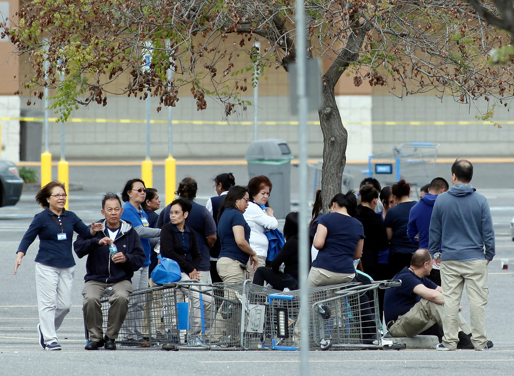 Description of . Walmart employees huddle in the parking lot outside the store on Story Road in San Jose, Calif., after a vehicle drove into the building and a driver reportedly began assaulting people in the store Sunday, March 31, 2013. (Karl Mondon/Staff)