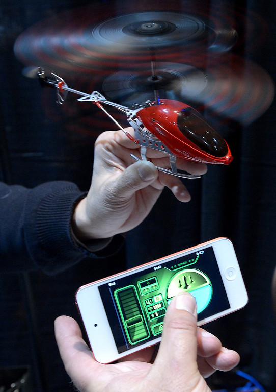 Description of . Thierry Dechatre of Avenir Telecom shows BeWii bluetooth operated heliccopter by iPhone during the opening event \'\'CES Unveiled\'\'  during the  International Consumer Electronics Show (CES) in Mandalay Bay Hotel resort on January 06, 2013 in Las Vegas, Nevada. (JOE KLAMAR/AFP/Getty Images)