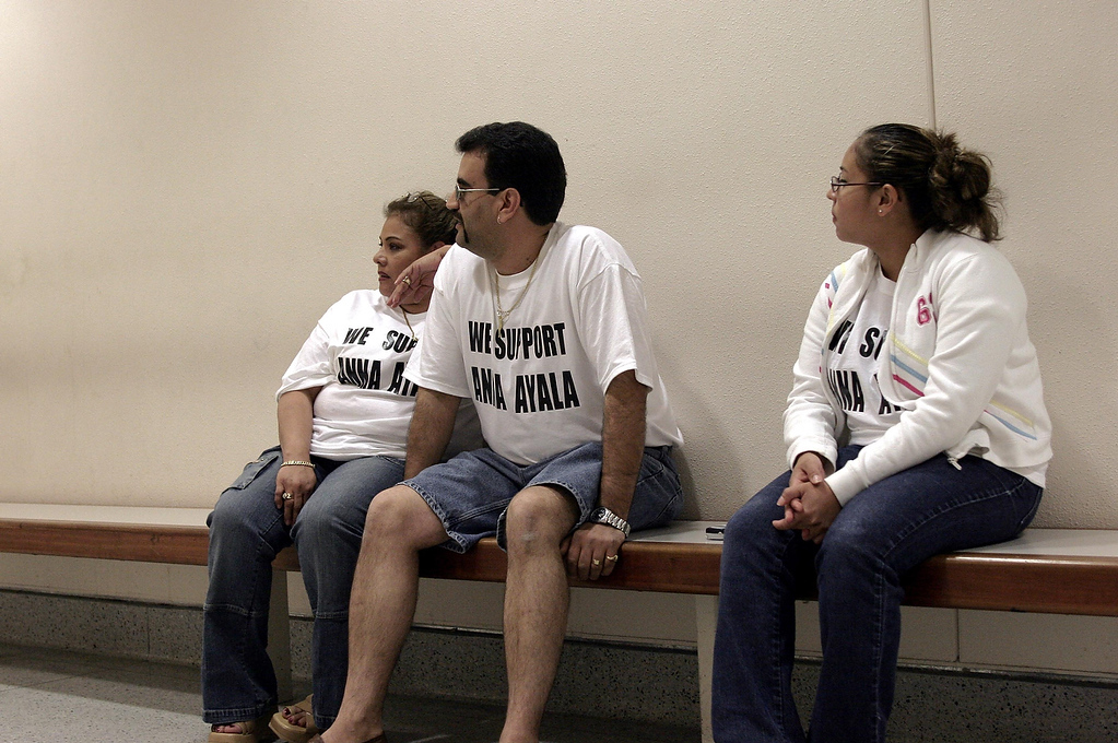 Description of . Anna Ayala's family members (names were not given) wait outside the  courtroom for Ayala's arraignment at the Santa Clara County Superior Court in  San Jose on May 9, 2005. About a dozen family and friends came to the  courthouse to show their support for Ayala, all wearing a t-shirt that said,
