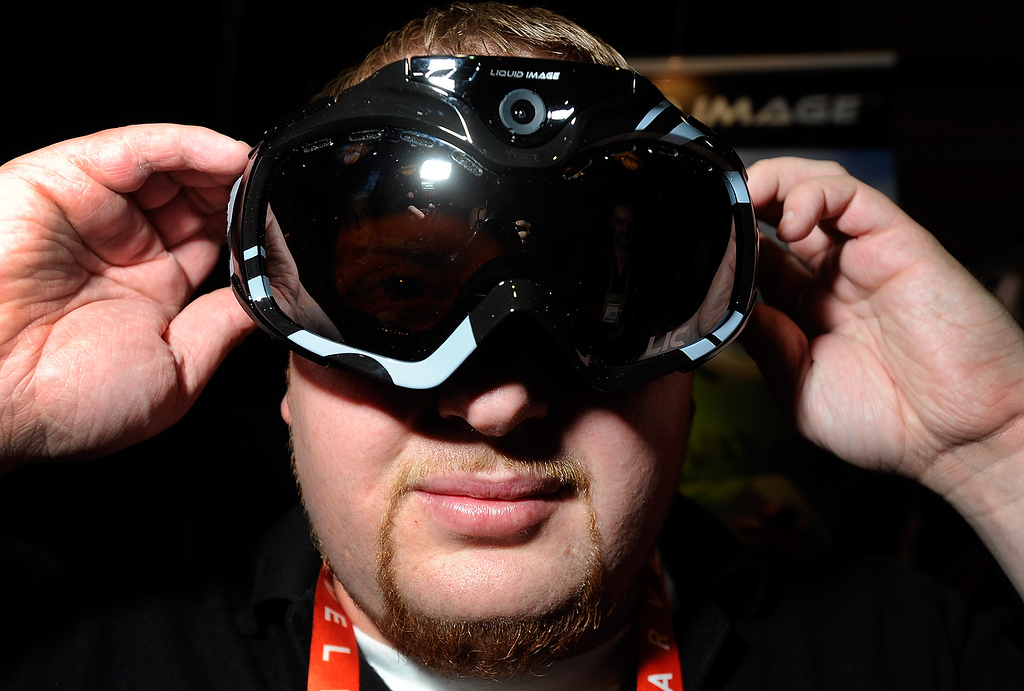 Description of . John Noonan displays a pair of Liquid Image goggles with a built in camera at a press event at the Mandalay Bay Convention Center for the 2013 International CES on January 6, 2013 in Las Vegas, Nevada. The goggles which have built-in WiFi are currently available on the market and have a retail price of USD 399. (Photo by David Becker/Getty Images)