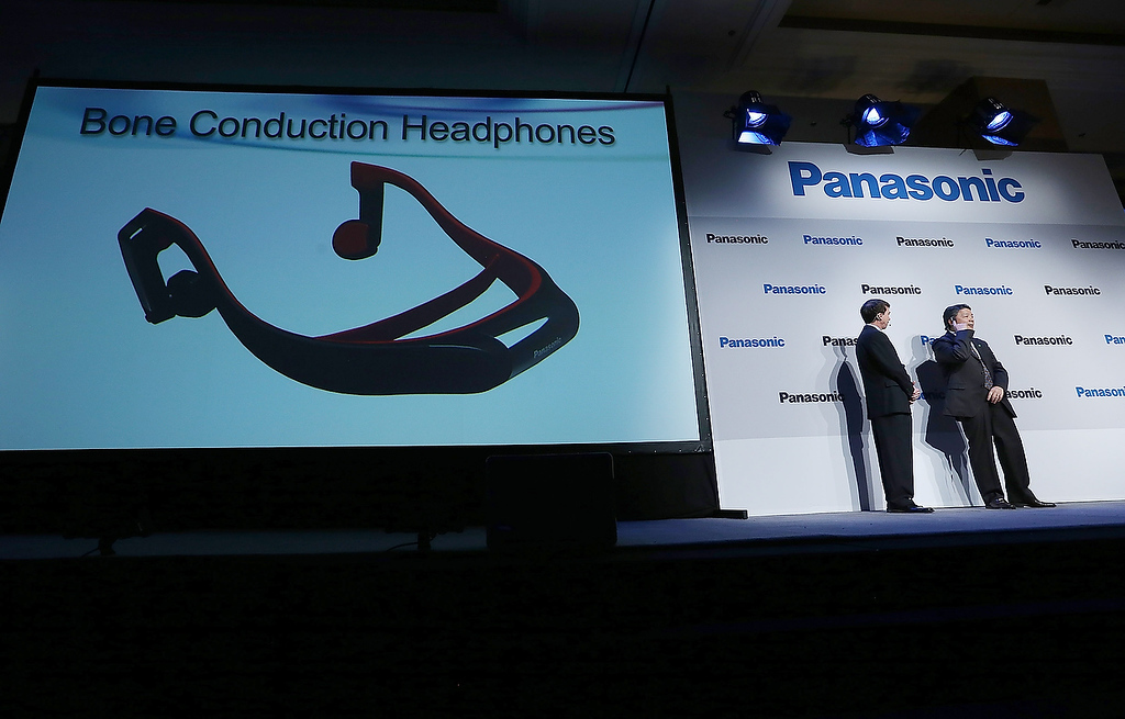 Description of . Shiro Kitajima (R), President of Panasonic Consumer Marketing Company of North America, demonstrates Bone Conduction Headphones at a Panasonic press conference during the 2013 International CES at the Mandalay Bay Convention Center on January 7, 2013 in Las Vegas, Nevada. (Photo by Justin Sullivan/Getty Images)