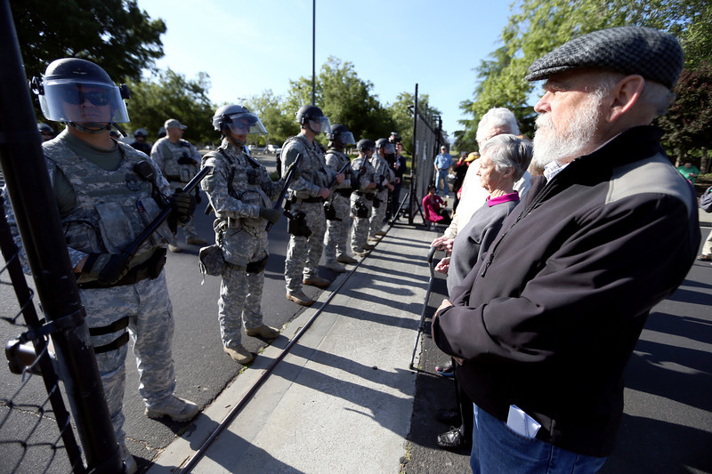 David McPhail, of Kensington, and other protesters block an entrance guarded by the National Nuclear Security Administration protective force at Lawrence Livermore Laboratory in Livermore, Calif., on Friday, April 18, 2014. (Anda Chu/Bay Area News Group)