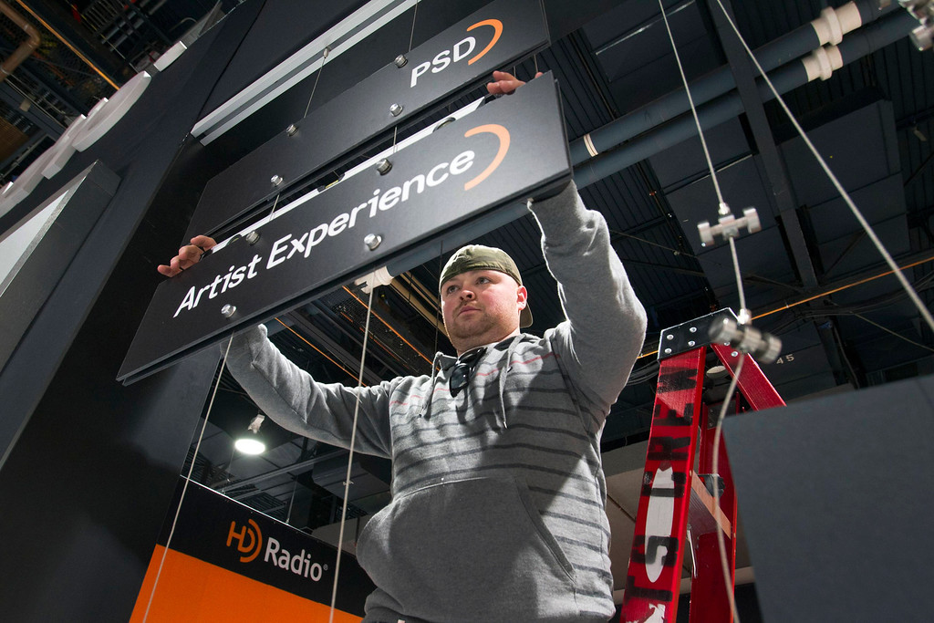 Description of . Juan Galdamez sets up an HD Radio booth for the International CES at the Las Vegas Convention Center in Las Vegas, Nev., on Jan. 5, 2013. (REUTERS/Steve Marcus)
