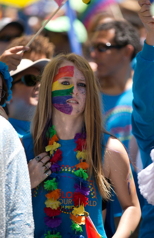 . An unidentified woman with her face painted in a rainbow scheme walks the route at the 44th annual San Francisco Pride Parade, Sunday, June 29, 2014 on Market Street in San Francisco. (D. Ross Cameron/Bay Area News Group)