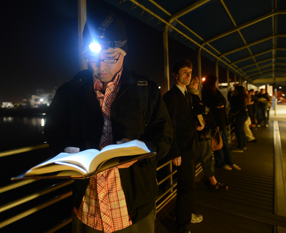 . Eric Tsujimoto, of Oakland, reads as he waits in line at the Alameda Main Street Ferry Terminal in Alameda, Calif., on Friday, Oct. 18, 2013. Tsujimoto arrived at 5 am for the 6 am ferry to San Francisco. BART workers went on strike at midnight after contract talks broke down, forcing commuters to find alternative ways to get to around the Bay Area. (Dan Honda/Bay Area News Group)