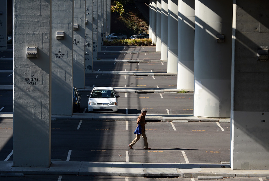 . A man walks through a mostly deserted parking lot at the Rockridge BART station in Oakland, Calif., on Monday, Oct. 21, 2013. (Kristopher Skinner/Bay Area News Group)