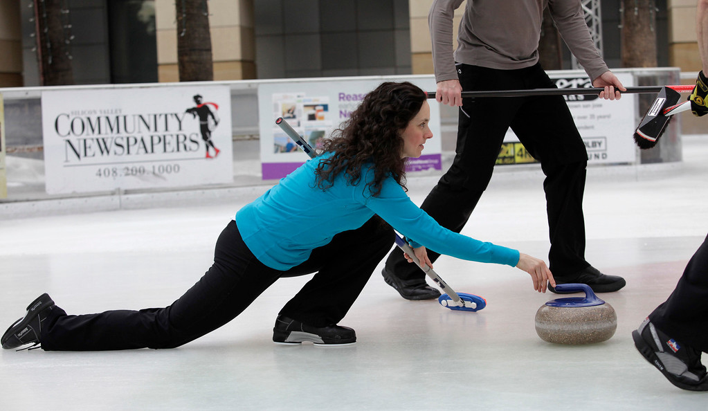 . Gabrielle Coleman of the San Francisco Bay Area Curling Club shows her form as she delivers a stone during a demonstration at Downtown Ice in San Jose, Calif. on Monday, January 6, 2014. With the Winter Olympic games at Sochi just weeks away, the local club wants to build awareness in the international sport. Coleman has competed on a national level at the 2009 Olympic trials. (Gary Reyes/Bay Area News Group)