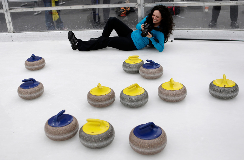 . Gabrielle Coleman photographs curling stones after members of the San Francisco Bay Area Curling Club demonstrate the sport of curling at Downtown Ice in San Jose, Calif. on Monday, January 6, 2014. Each stone weighs about 40 pounds. With the Winter Olympic games at Sochi just weeks away, the local club wants to build awareness in the international sport. Coleman has competed at the national level having tried out for the U.S. Olympic curling team in 2009. (Gary Reyes/Bay Area News Group)