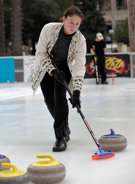 . Davinna Kong of the San Francisco Bay Area Curling Club sweeps the ice as a stone is delivered down the ice during a demonstration at Downtown Ice in San Jose, Calif. on Monday, January 6, 2014. With the Winter Olympic games at Sochi just weeks away, the local club wants to build awareness in the international sport. Kong competes at the club level and national level. (Gary Reyes/Bay Area News Group)