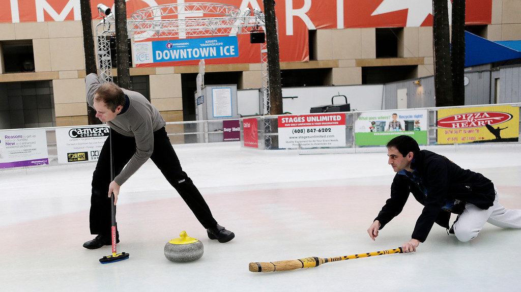 . Richard Lazarowich, right, delivers as stone as Stephen Marschall sweeps as members of the San Francisco Bay Area Curling Club demonstrate the sport of curling at Downtown Ice in San Jose, Calif. on Monday, January 6, 2014. With the Winter Olympic games at Sochi just weeks away, the local club wants to build awareness in the international sport. (Gary Reyes/Bay Area News Group)