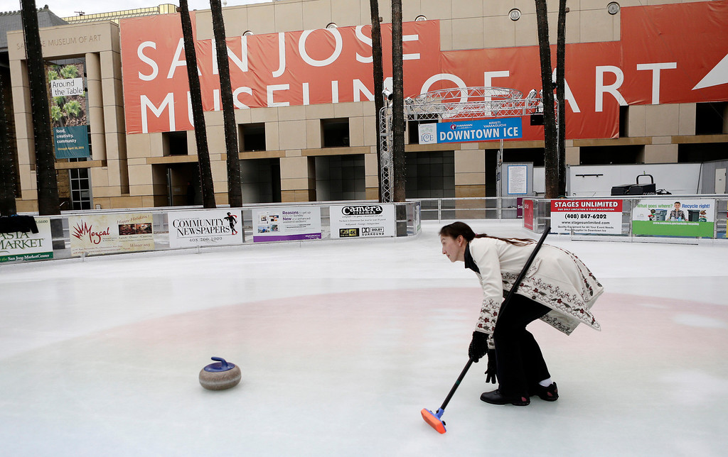 . Davinna Kong of the San Francisco Bay Area Curling Club coaxes her stone following her delivery during a demonstration at Downtown Ice in San Jose, Calif. on Monday, January 6, 2014. With the Winter Olympic games at Sochi just weeks away, the local club wants to build awareness in the international sport. Kong competes at the club level and national level. (Gary Reyes/Bay Area News Group)