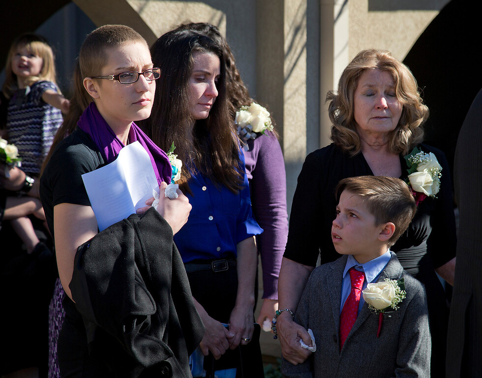 . At left, Dale Smith\'s daughter Crystal Christensen waits as caskets are ready to be placed in the hearses after the funeral for Silicon Valley tech executive and avid pilot Dale Smith and four family members at the LDS Church in San Jose, Calif., on Saturday, Feb.1, 2014.  A plane piloted by Smith crashed on Dec. 1, 2013 carrying his daughter Amber Smith and her fiancee, Jonathan Norton; and son Daniel Smith and his wife, Sheree.  (LiPo Ching/Bay Area News Group)