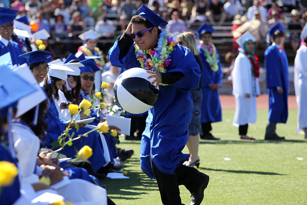 . A Irvington High School graduates retrieves a wayward beach ball during their commencement ceremony in Fremont, Calif., on Thursday, June 20, 2013. (Anda Chu/Bay Area News Group)