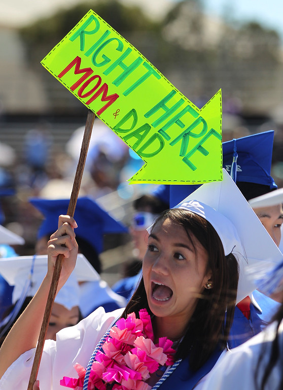 . Melanie Tsoi, 18, Irvington High School graduate and student body president holds up a sign to help her parents find her during their commencement ceremony in Fremont, Calif., on Thursday, June 20, 2013. (Anda Chu/Bay Area News Group)